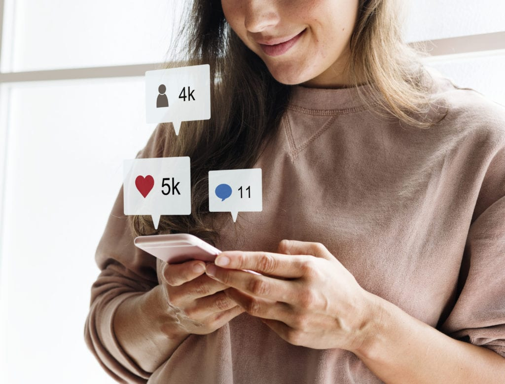 Woman using a smartphone social media receiving likes, comments, and followers