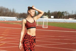 beautiful caucasian girl athlete resting after jogging on a running track. Healthy lifestyle. Slimming