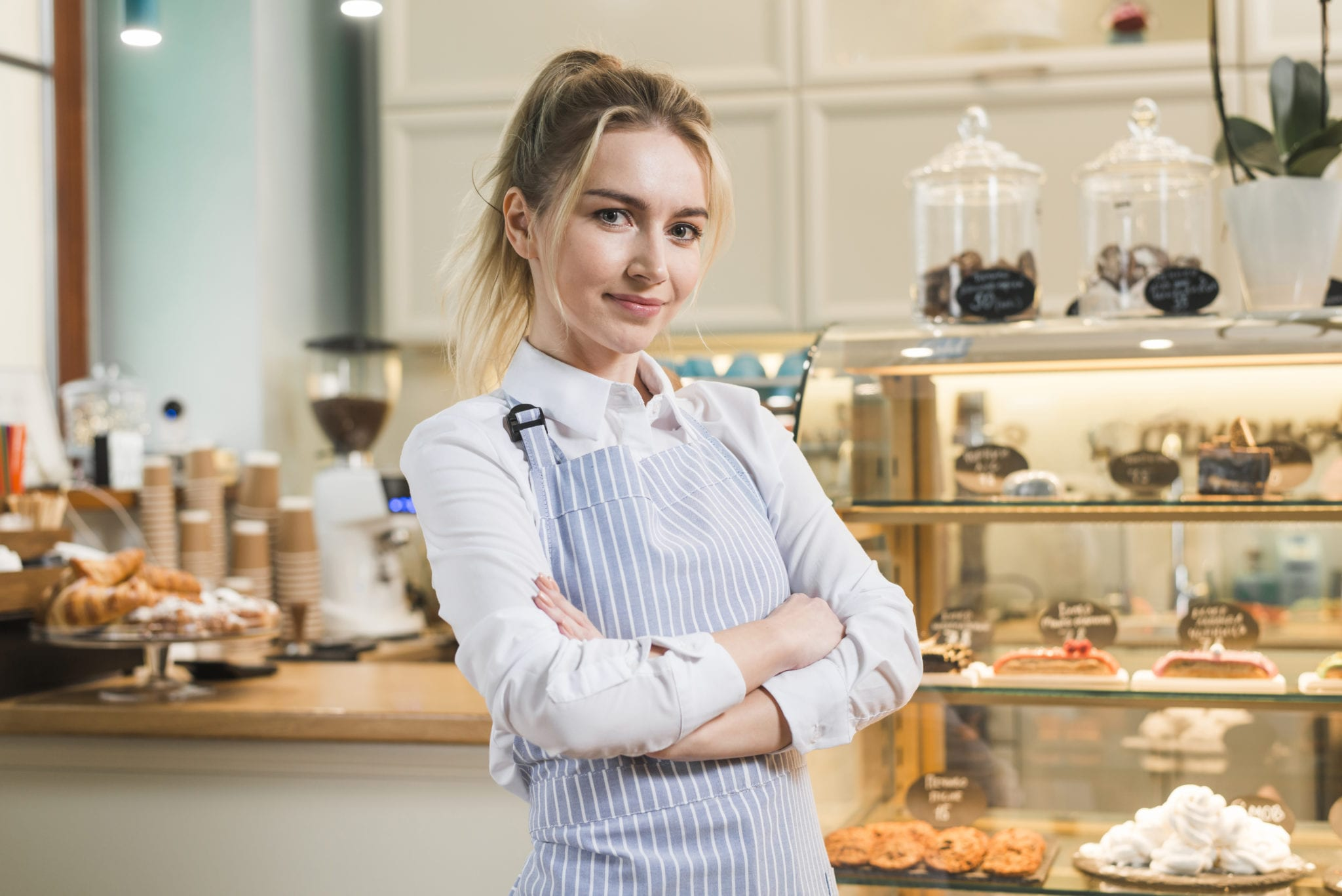 female small business owner standing in her coffee shop with arms crossed